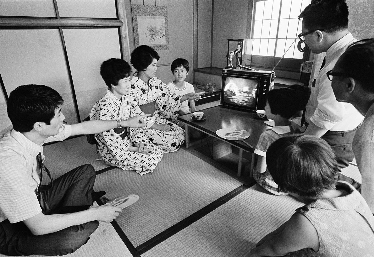 In Tokyo, a Japanese family watches a live television broadcast of the Apollo 11 astronauts saluting ...