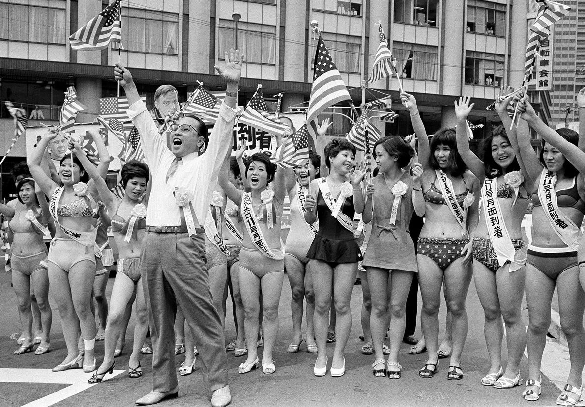 Outside the U.S. Embassy in Tokyo, Japan, a group of cabaret dancers and their manager cheer ...