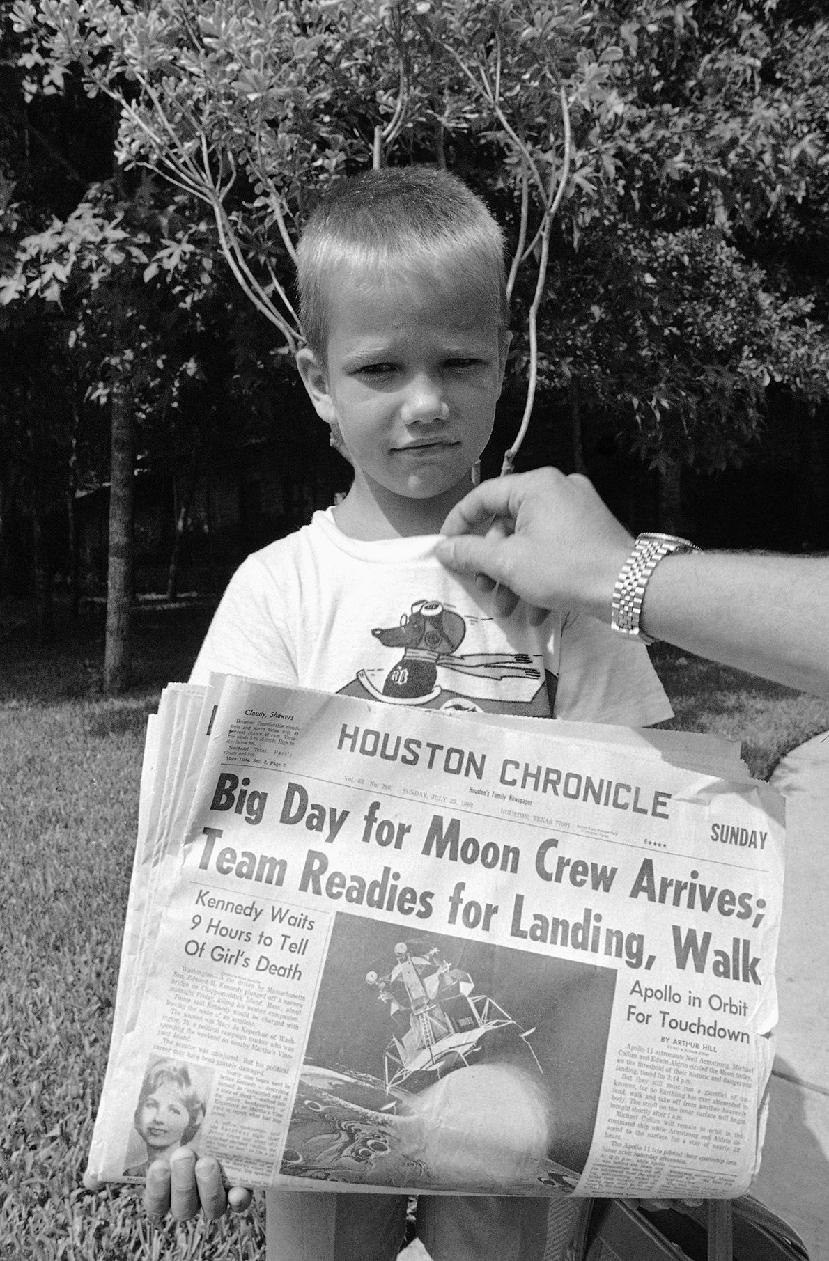 Six-year-old Mark Armstrong, son of Apollo 11 astronaut Neil Armstrong, holds the morning newspaper at the ...
