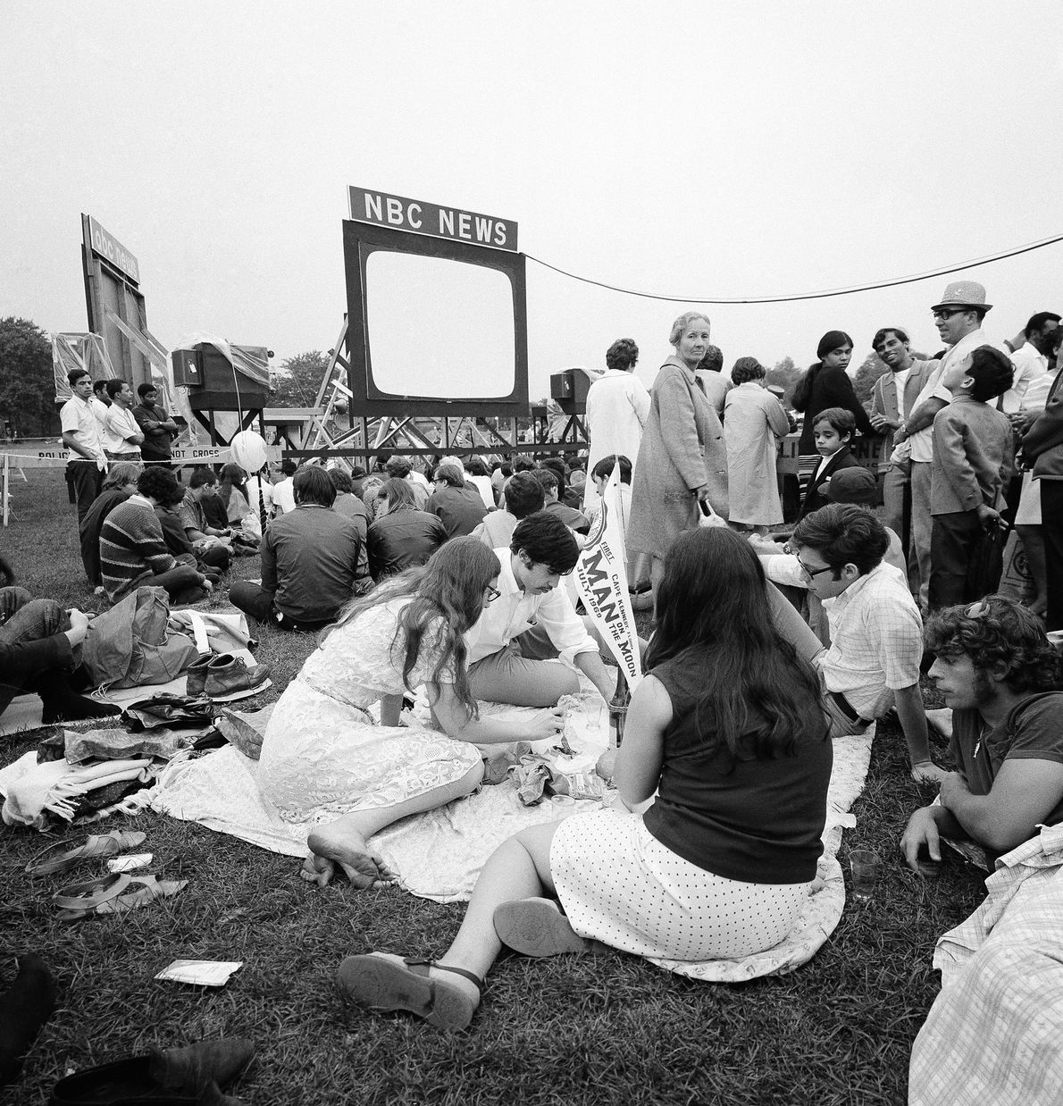 In New York City's Central Park, a crowd watches on an open-air screen as the Apollo ...