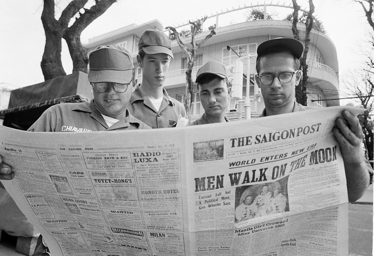 U.S. servicemen pause in Saigon on July 21, 1969, to read a local newspaper account of ...
