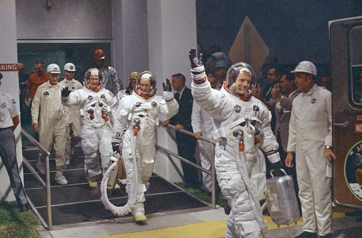 Waving at the front of the line, astronaut Neil Armstrong heads for the van that will ...
