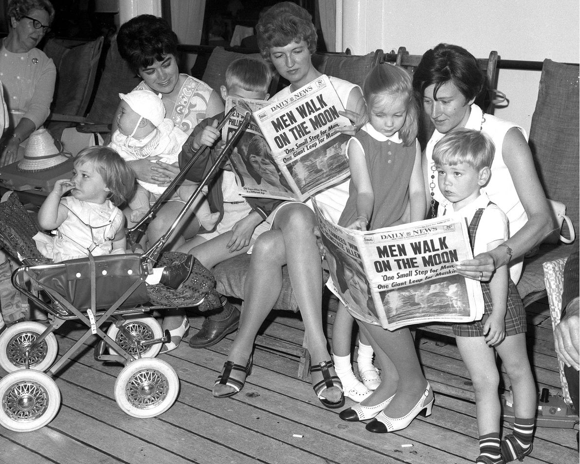 Mothers and children huddle on Pier 92 in New York City to read the Daily News. ...