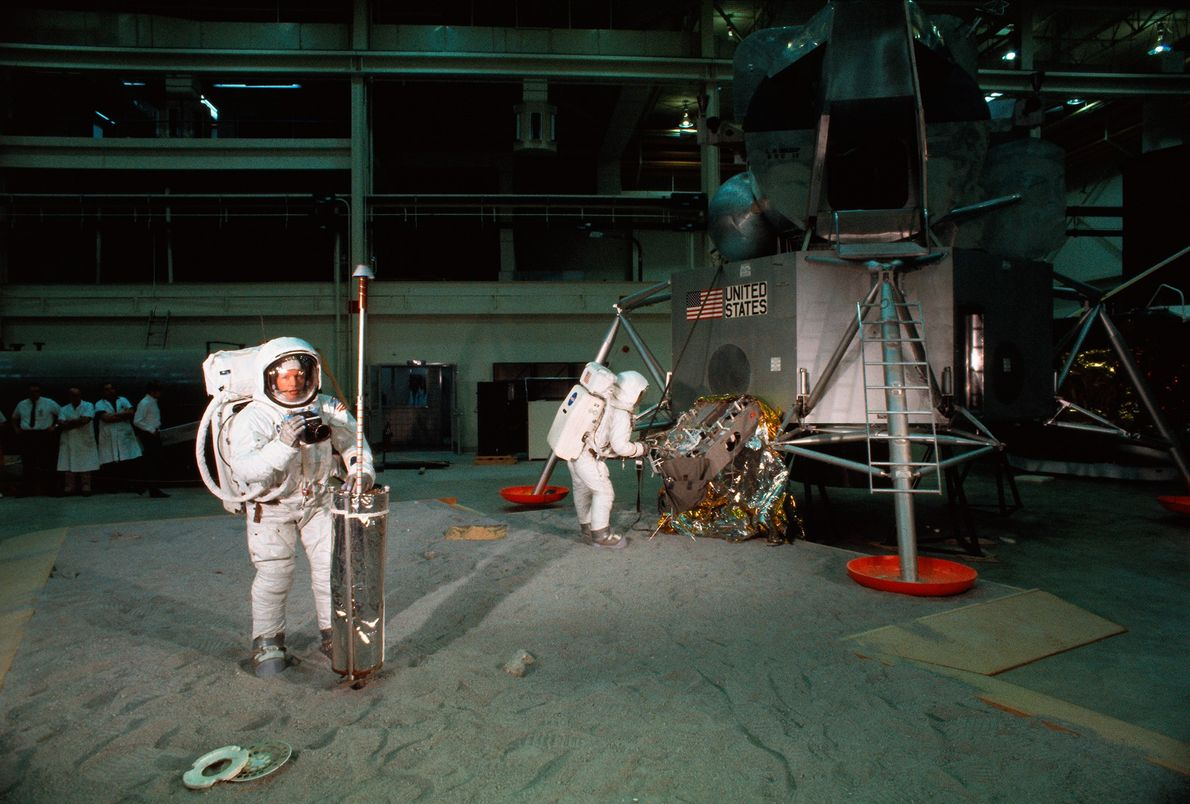 With a mockup of the lunar module in the background, the Apollo 11 astronauts run through ...