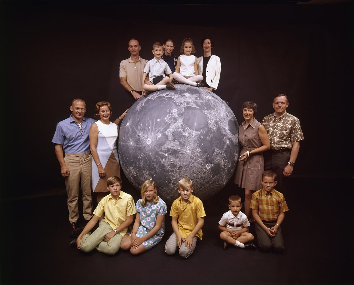 The three Apollo 11 astronauts pose with their families on a model of the moon in ...