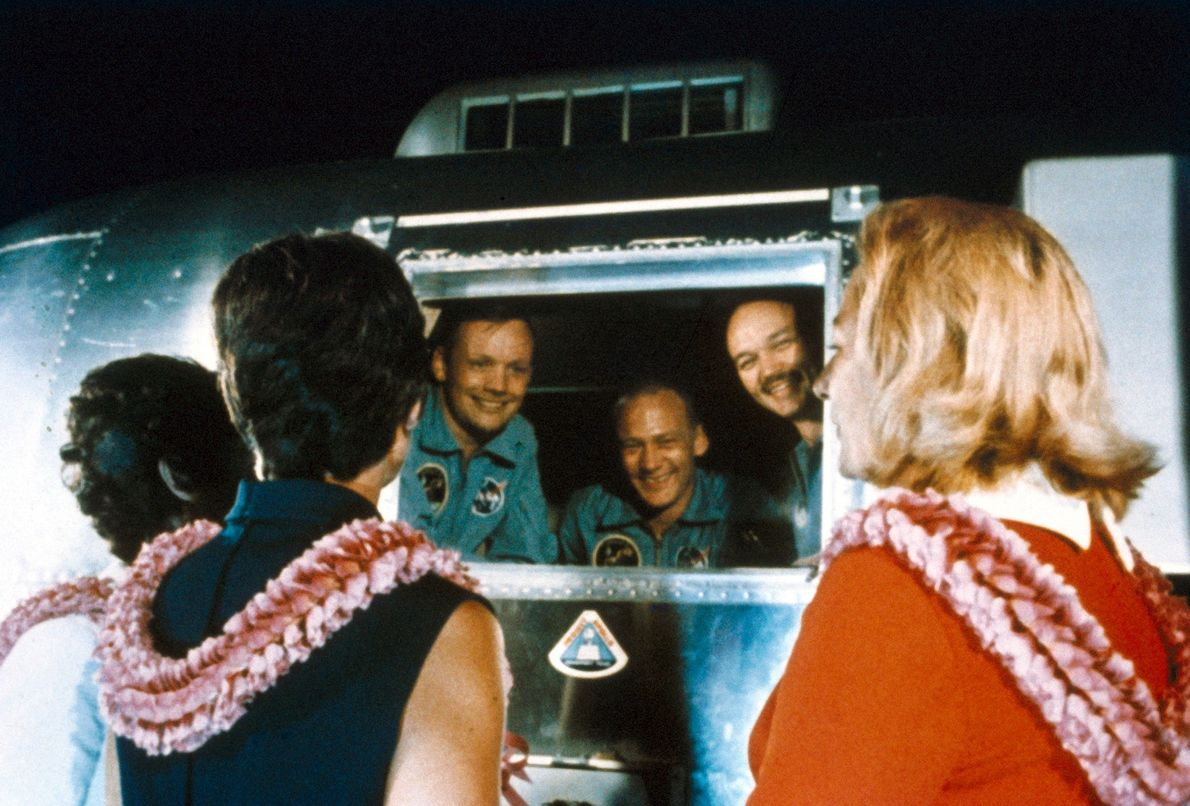 Astronauts Neil Armstrong, Buzz Aldrin, and Michael Collins greet their wives from the Mobile Quarantine Facility ...