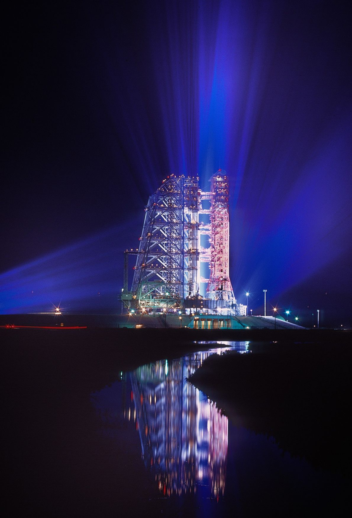 Reflected in a pond, the Apollo 11 spacecraft sits high atop the Saturn V rocket on ...