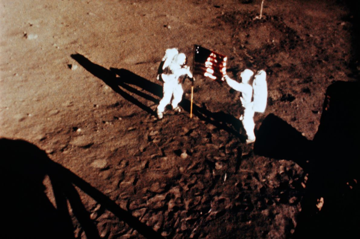 Astronauts Neil Armstrong and Buzz Aldrin erect a U.S. flag on the surface of the moon ...