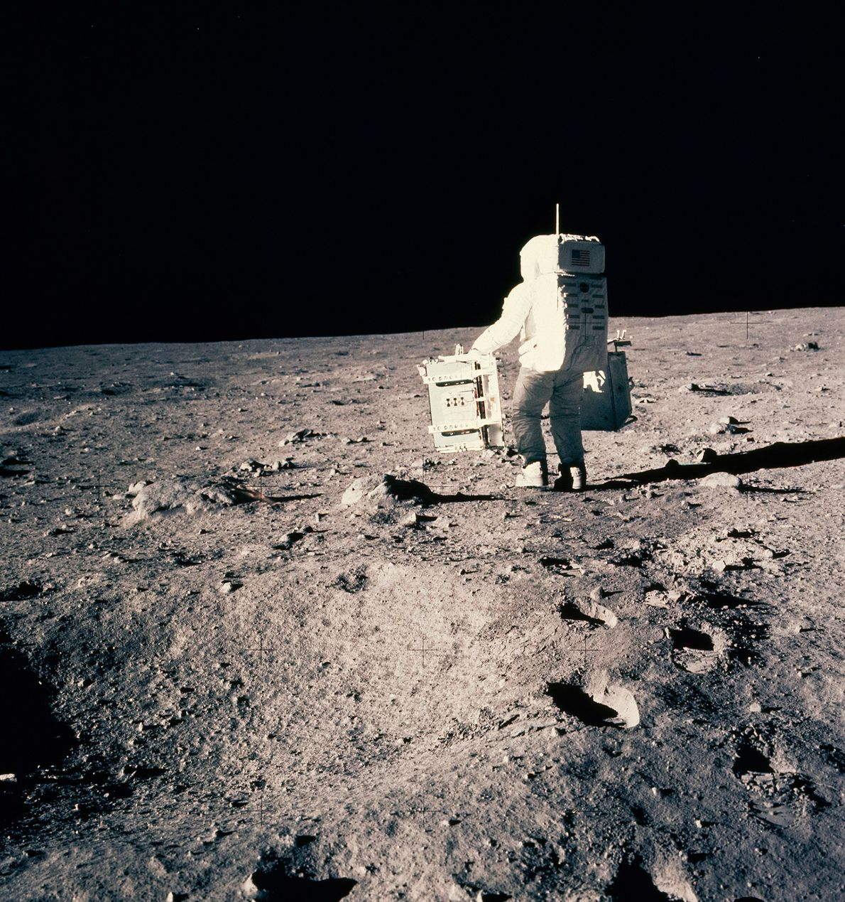 Astronaut Buzz Aldrin prepares to deploy two components of the Early Apollo Scientific Experiments Package on ...