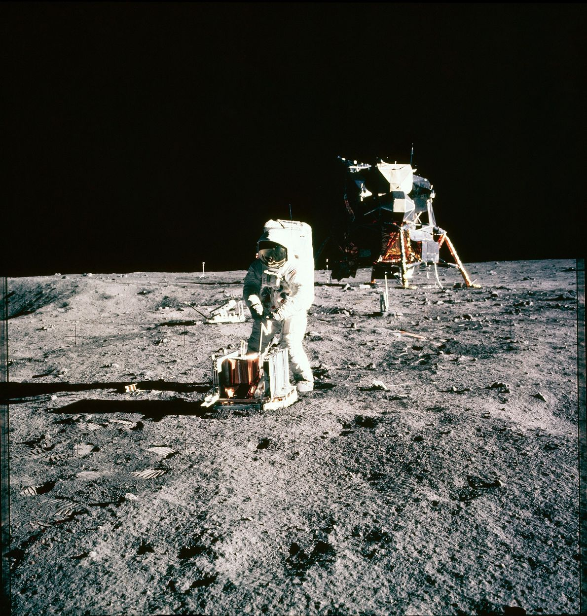 "Astronaut Buzz Aldrin sets up a seismic unit—a tool used to measure ""moonquakes""—on the lunar surface. ..."