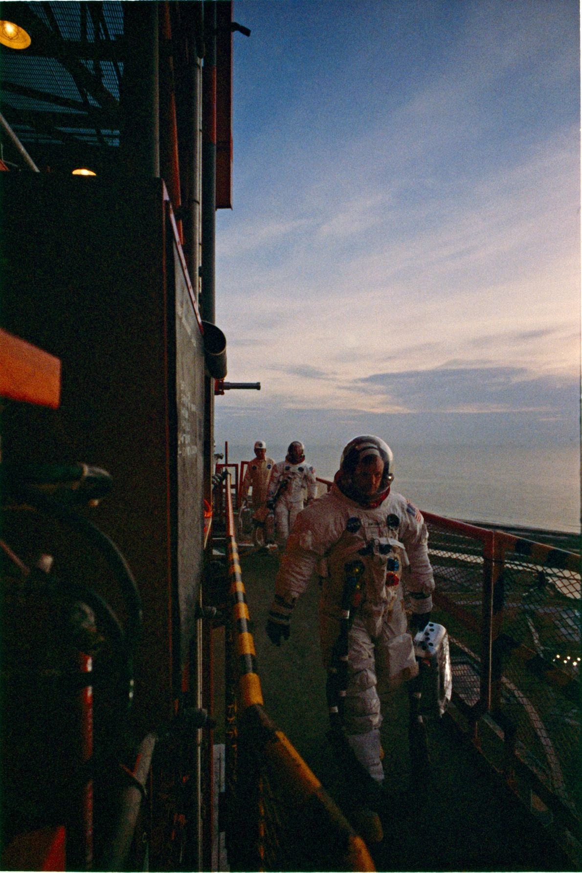 Dressed in their flight suits, the Apollo 11 crew members walk toward the spacecraft at sunrise ...