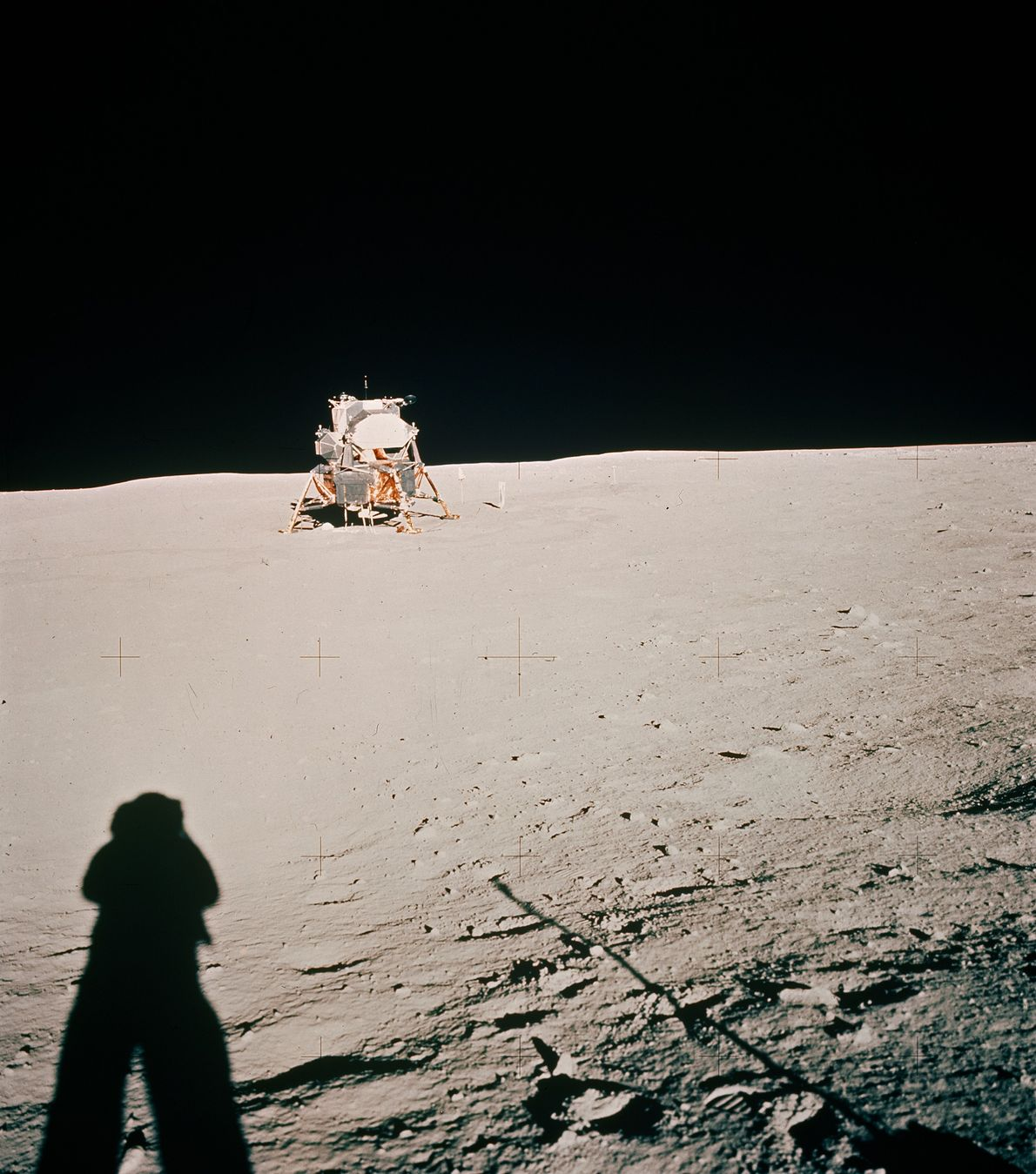 "Astronaut Neil Armstrong's shadow stretches across the moon toward the lunar module, the Eagle. ""Crosses on ..."