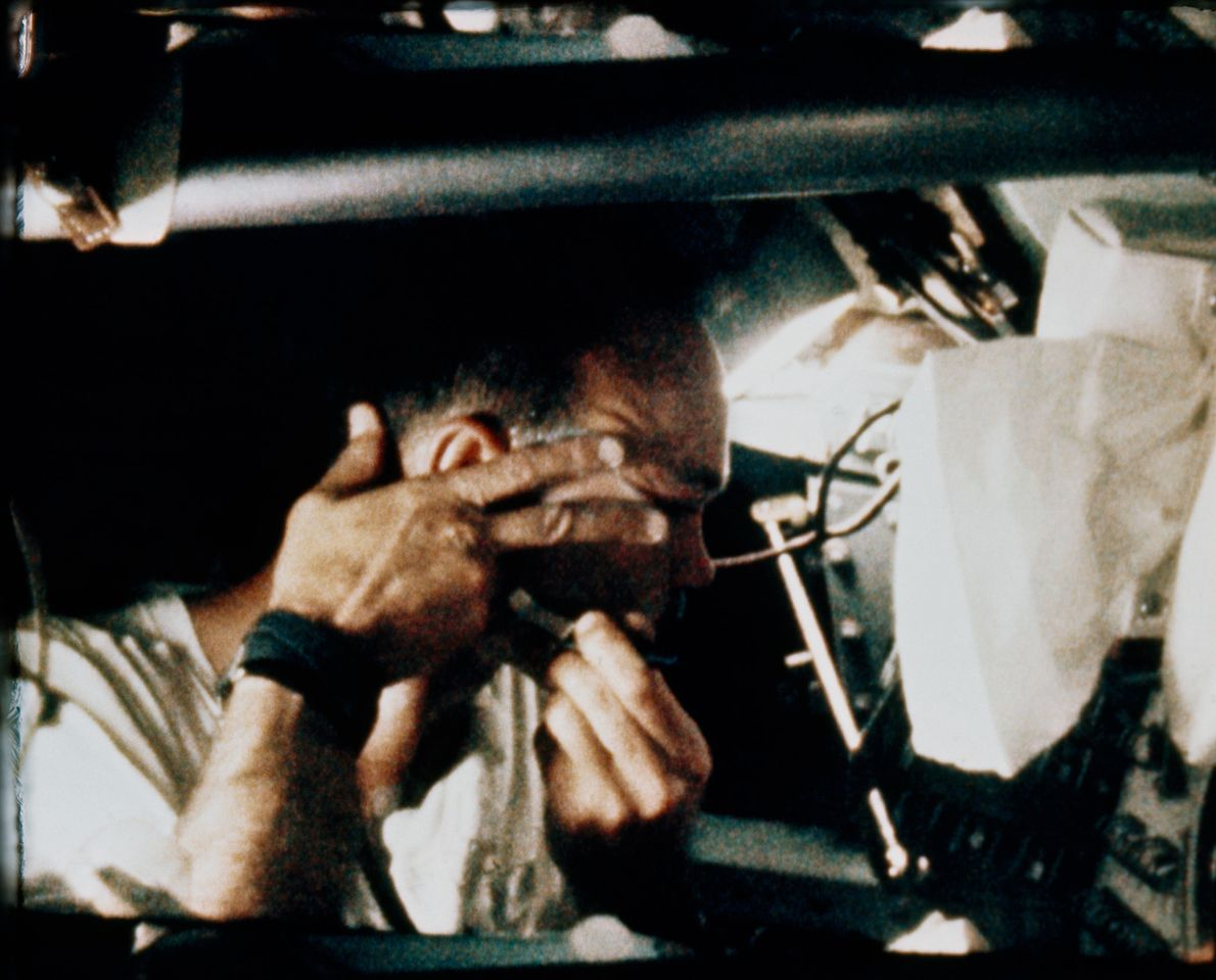 Still aboard the Apollo 11 spacecraft, astronaut Michael Collins shaves his face prior to splashdown on ...