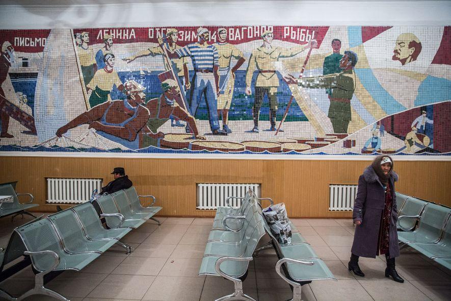 People wait for a train under a Soviet-era mural in Aralsk.