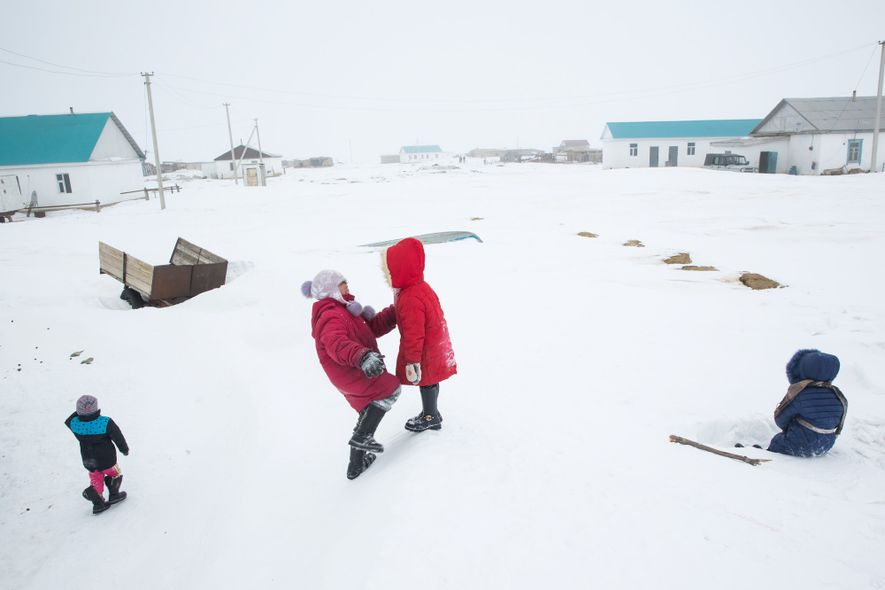 Children play on a snowdrift in Tastubek, Kazakhstan, where economic opportunities are improving with the health ...