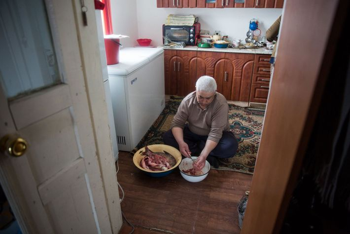 Kiderbai Ibragimov, 45, prepares a fish meal at home in Tastubek.