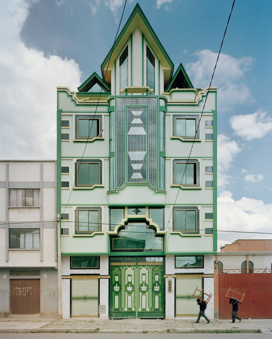 Men are dwarfed by one of Mamani's emerald buildings.  ...
