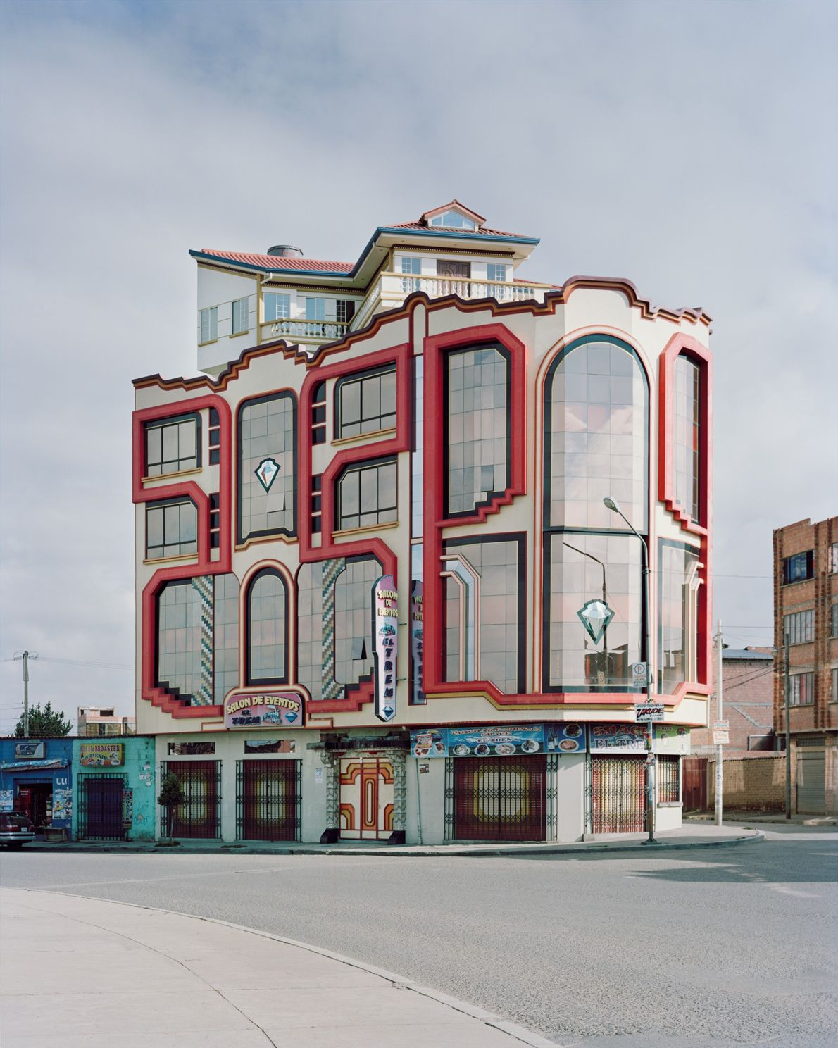 One of Mamani's gleaming chrome and bright acrylic facades pops against El Alto's mud brick and ...