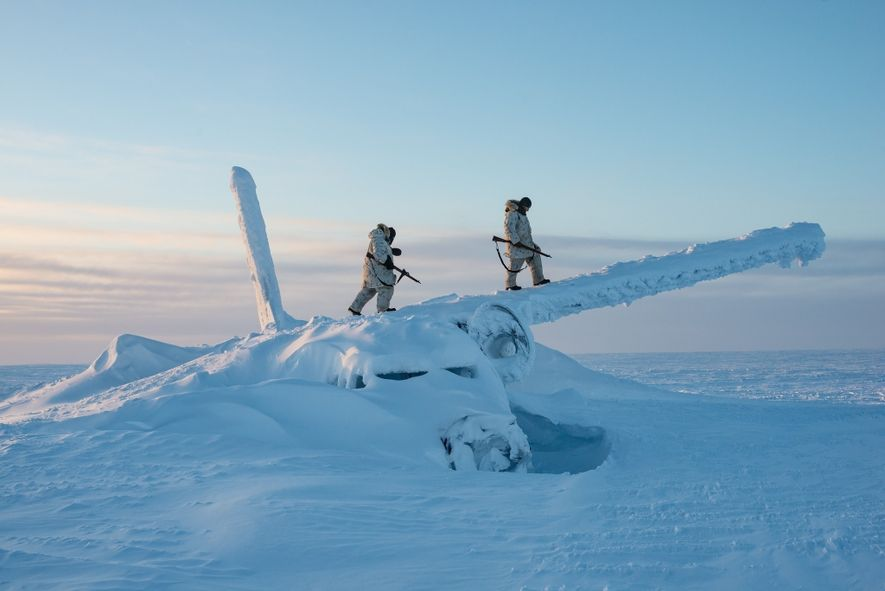 Canadian soldiers climb on the wreckage of a plane, roughly a thousand miles south of the ...
