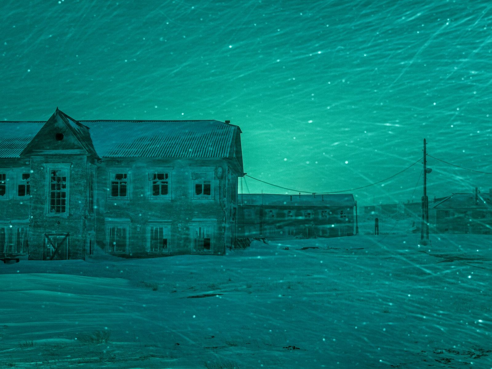 Wind-blown snow swirls past abandoned buildings keeping cold vigil over the empty streets of Dikson. Once ...