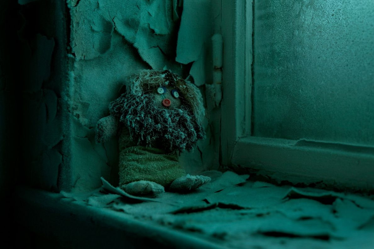 A homemade doll leans against a frosty windowsill of an abandoned school in Dikson. In its ...