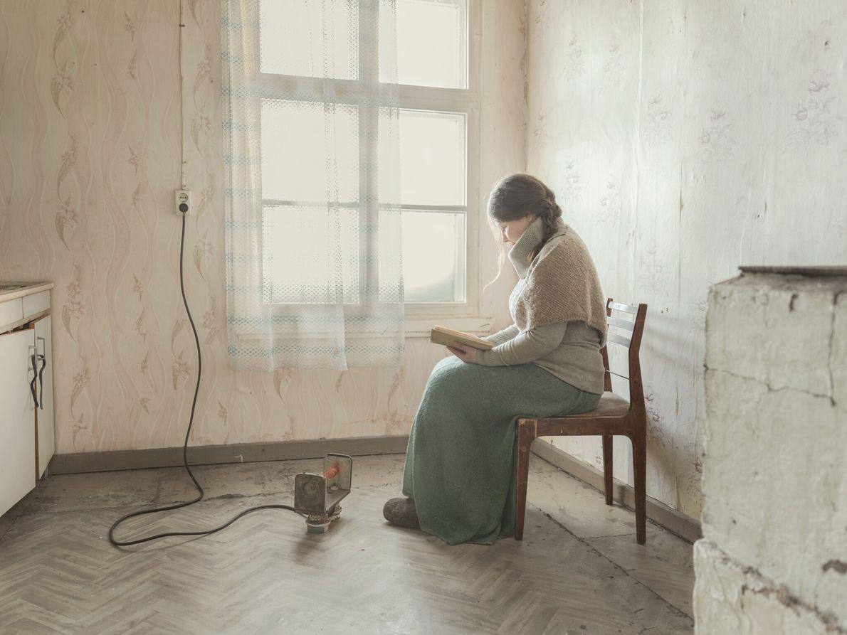 Kostikova keeps warm by a small radiator as she reads her book. When Kostikova was a ...