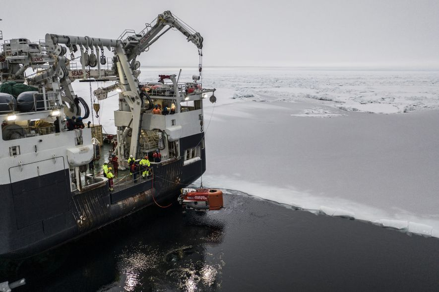 The bright orange Nereid Under Ice vehicle gets lowered into Arctic waters from the Kronprins Haakon. ...