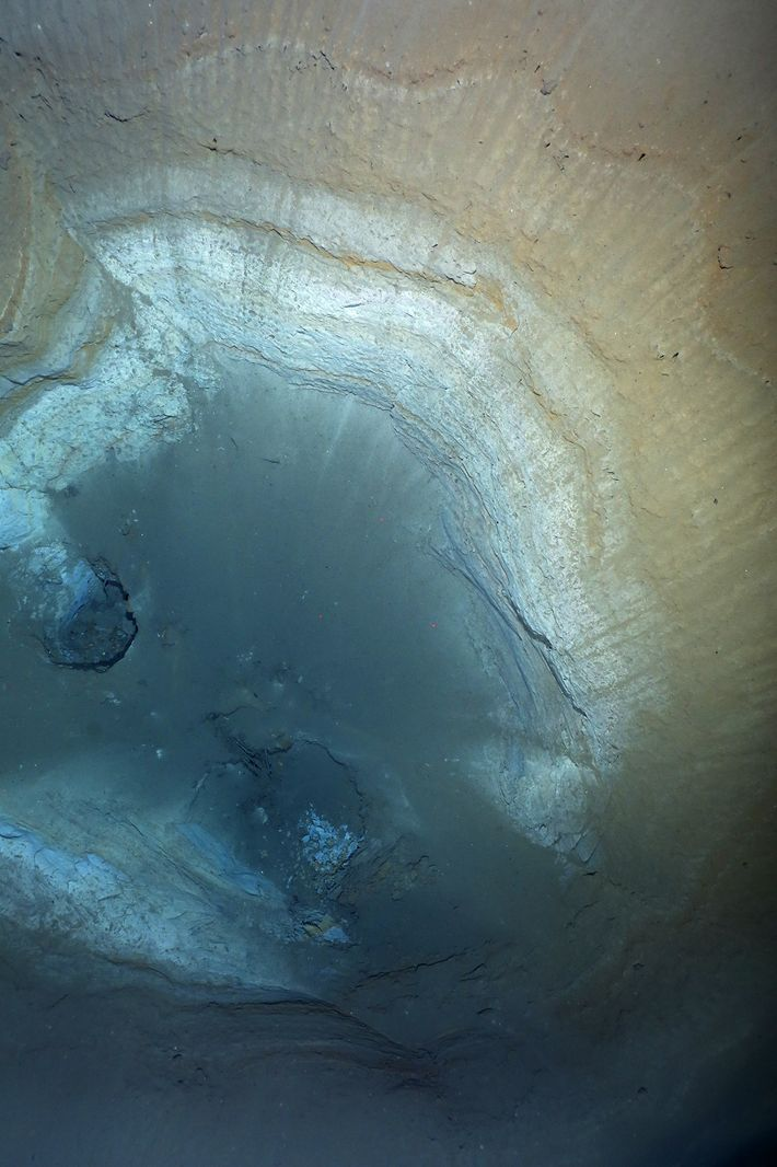A view into a sinkhole in the Aurora hydrothermal field sediments shows geologic layers going back ...
