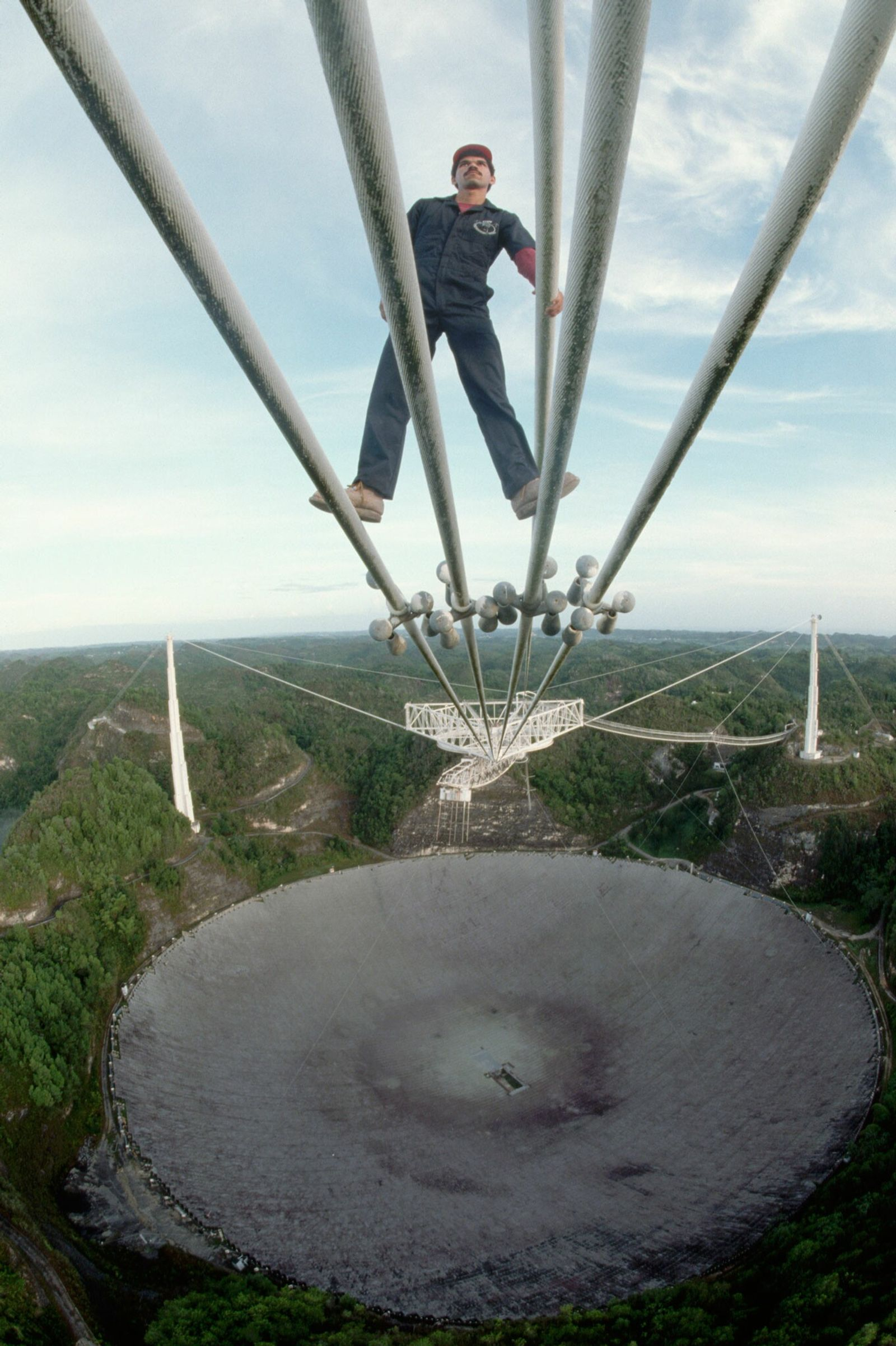 Technician Luis Heredia checks some the cables which suspend the receiver over the radio telescope dish ...