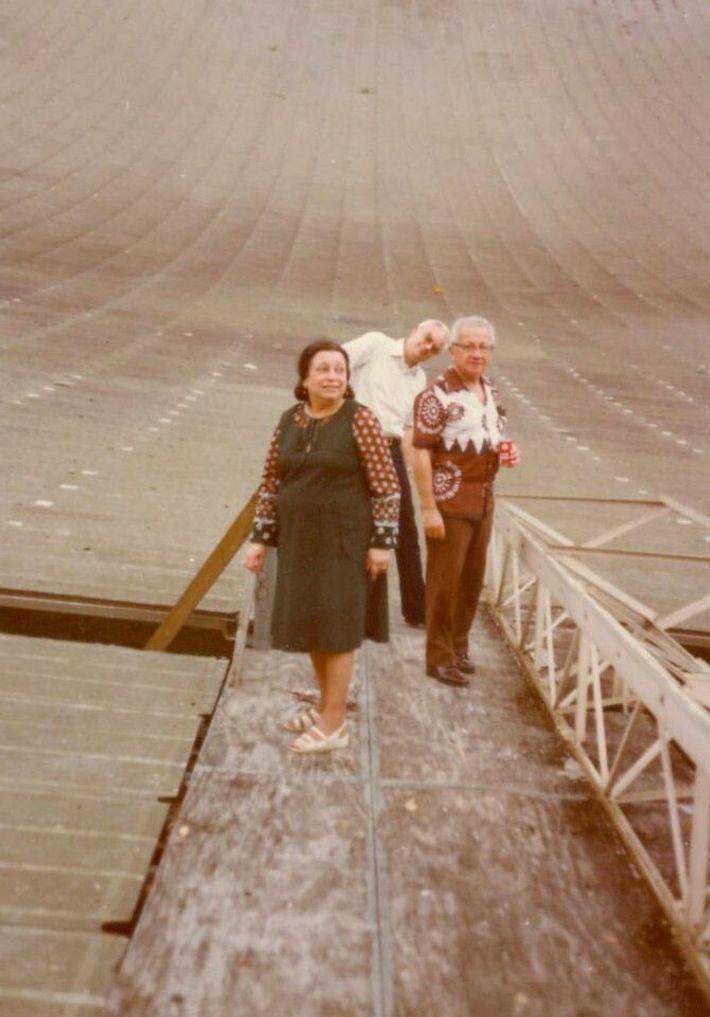 Frank Drake shows family members Zekin and Adma Shakhashiri around the telescope's giant dish.