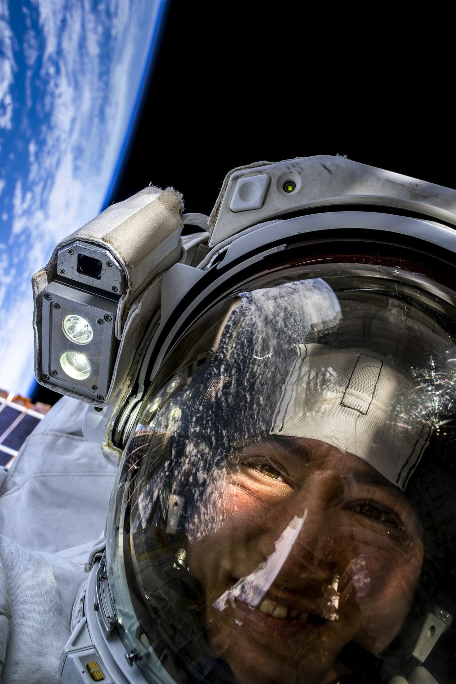 NASA astronaut Christina Koch takes a space selfie with Earth behind her. She and fellow NASA ...