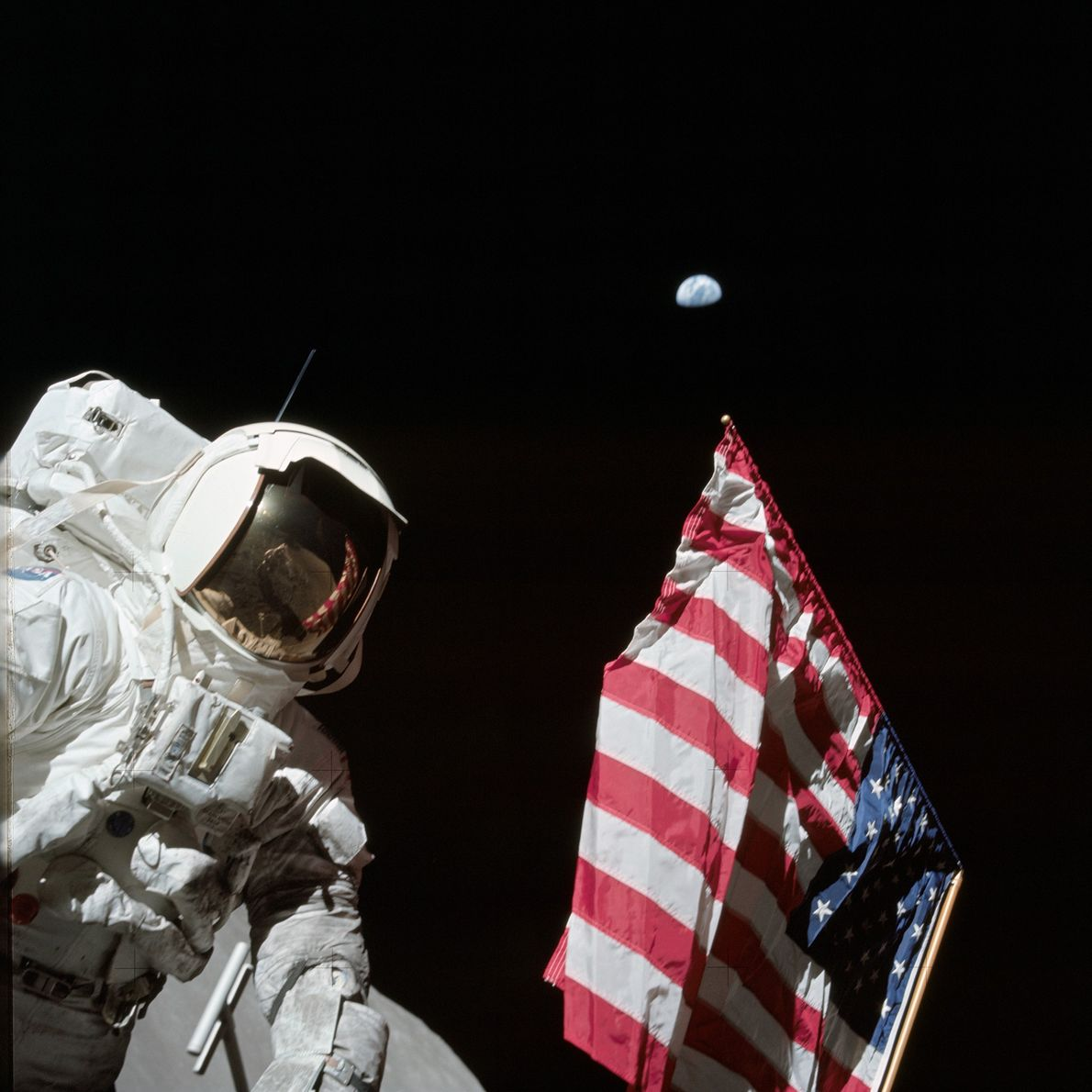 Apollo 17 astronaut Harrison H. Schmitt stands next to a United States flag during a moon ...