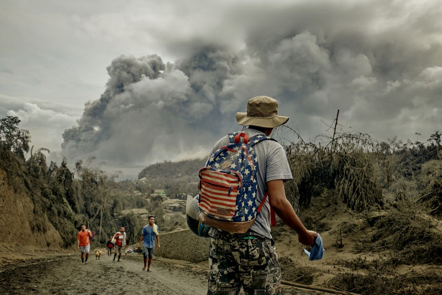 Residents flee their village as plumes of smoke cover the sky from the eruption of Taal ...