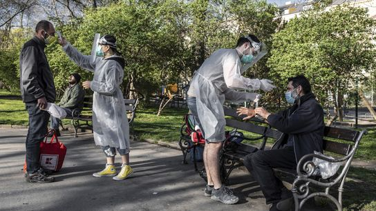 Medical students attend to people experiencing homelessness in a park in Prague during the COVID-19 pandemic.