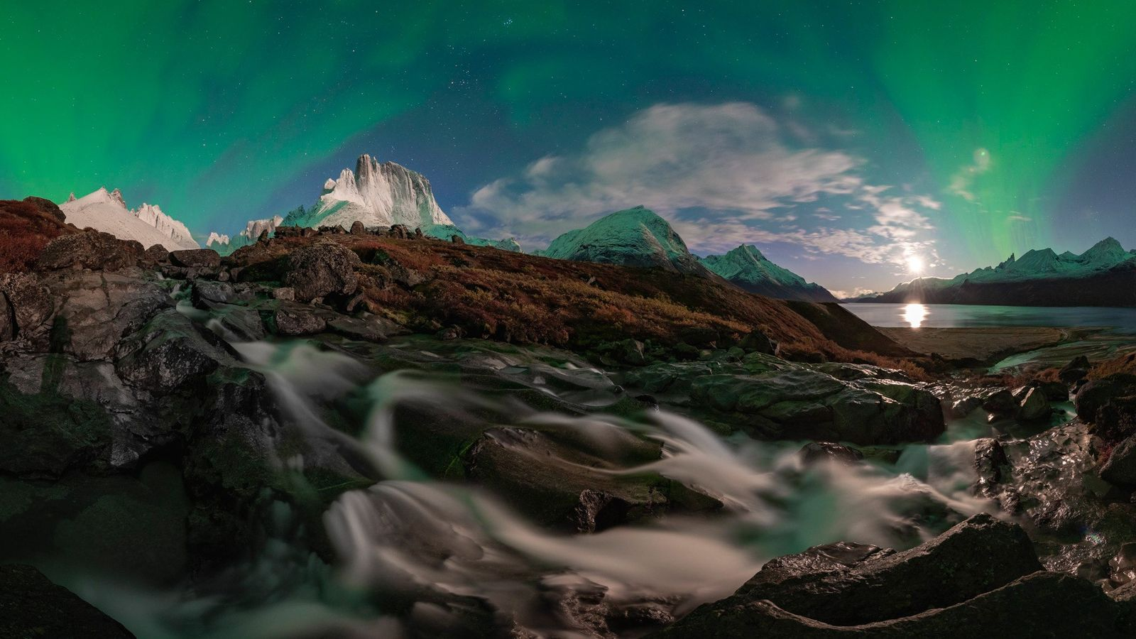 An aurora blazes against the night sky near the Tasermiut Fjord. The fjord has well-known mountains, ...