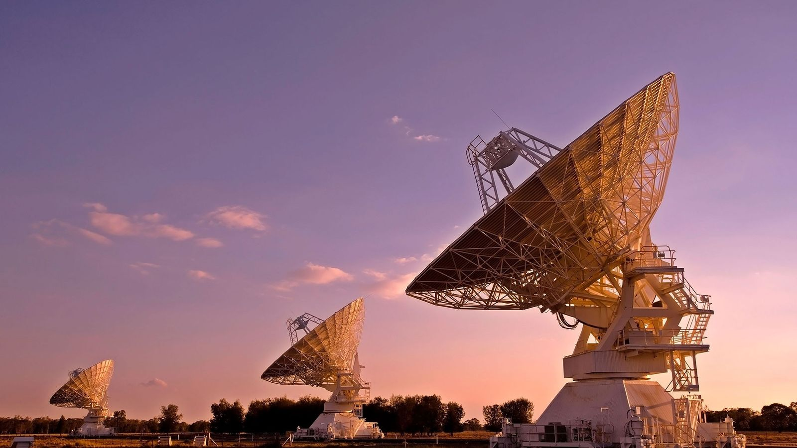 The sun sets on the Australian outback behind the Australia Telescope Compact Array, a series of ...