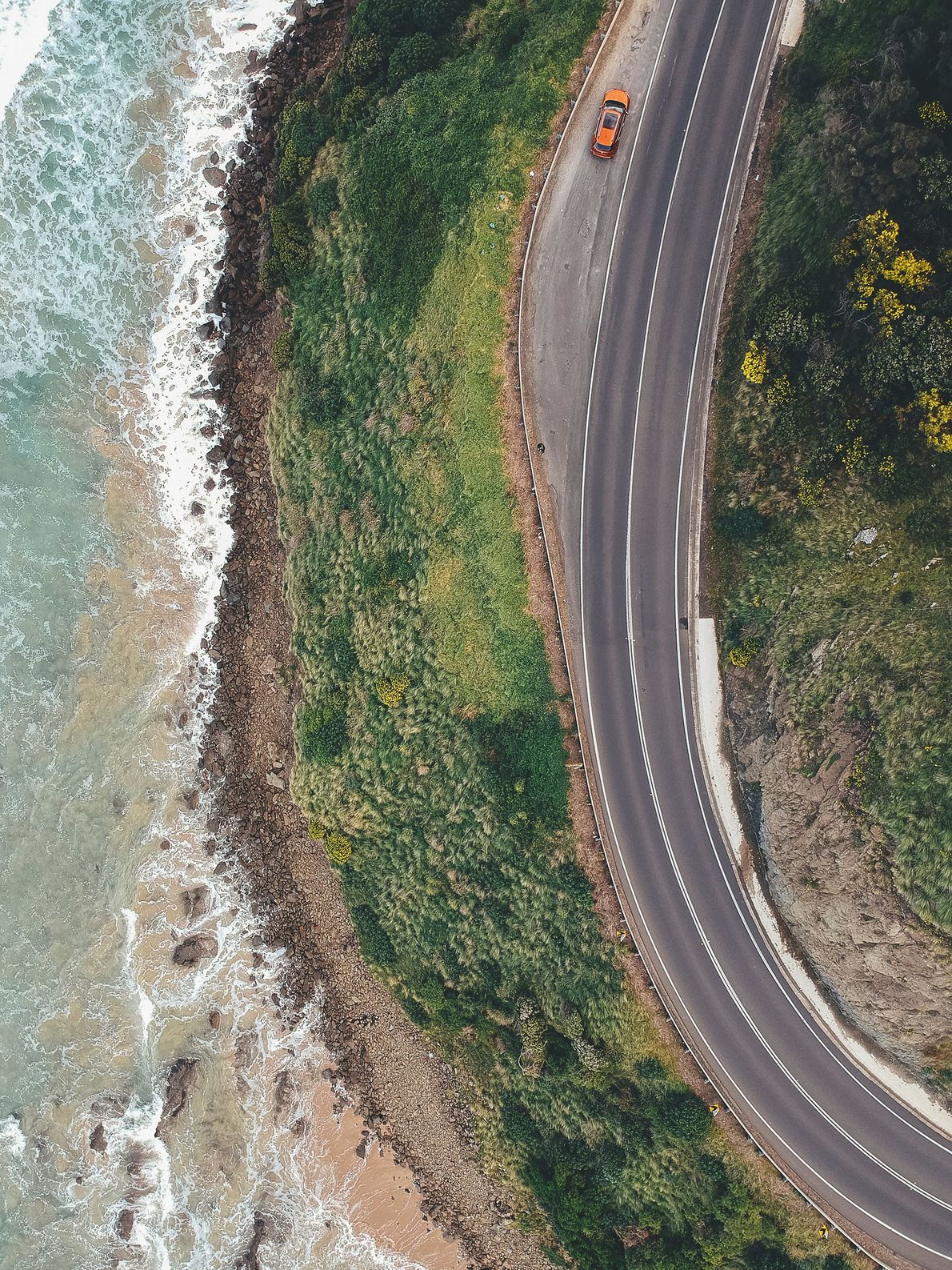 Aerial view of the Great Ocean Road as it curves to meet the beach along the southern coast of Australia.