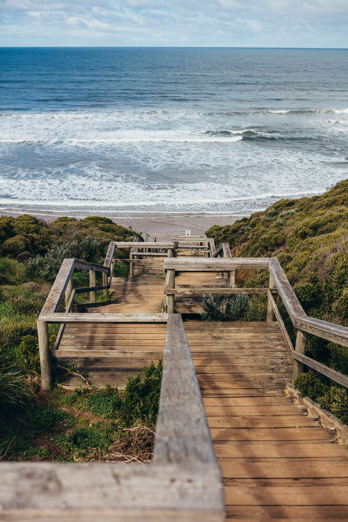Sun-bleached wooden steps leading down to Bells Beach.