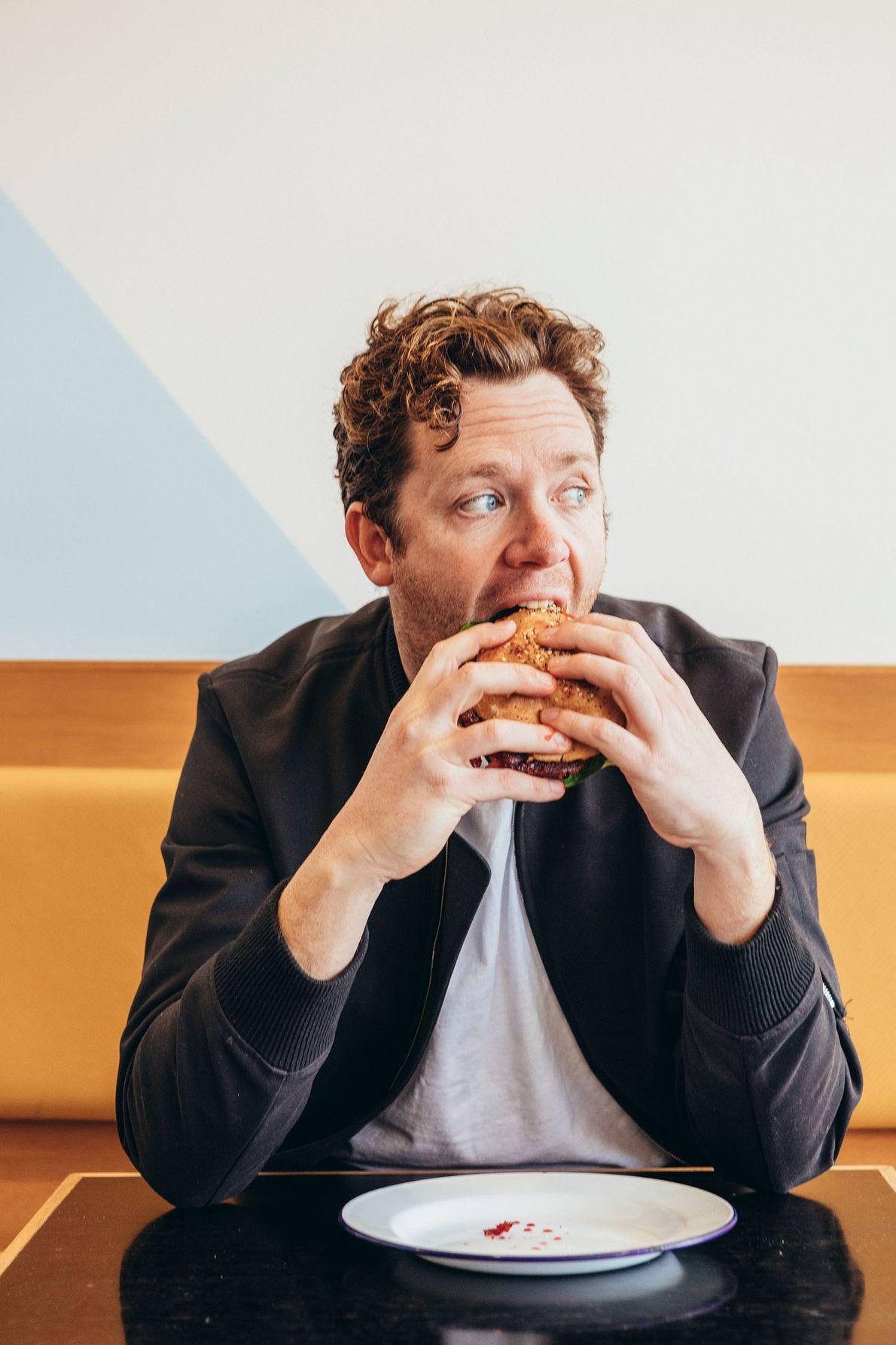 Brett Graham, owner of The Bottle of Milk burger bar in Lorne, tucks into The B.O.M ...