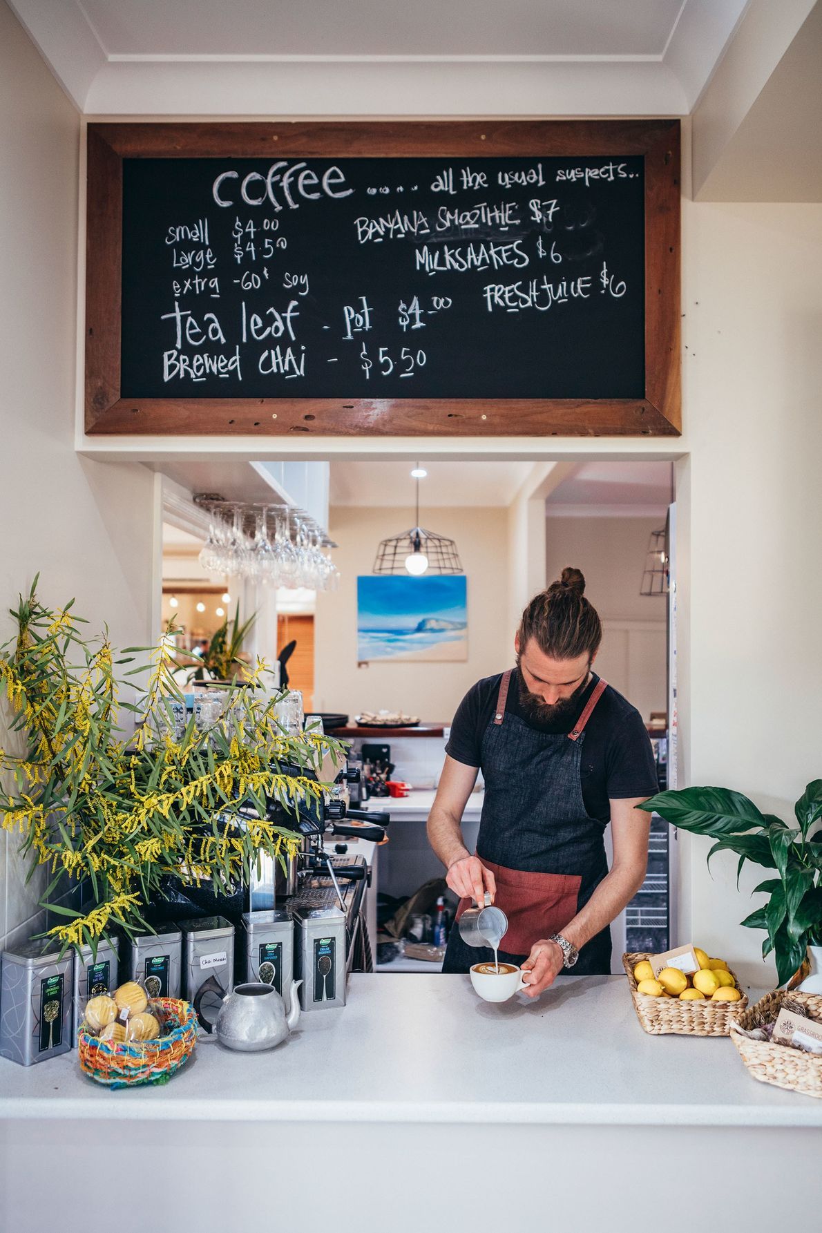 A barista pours a flat white at the Grassroots Deli Cafe in Port Campbell — a ...