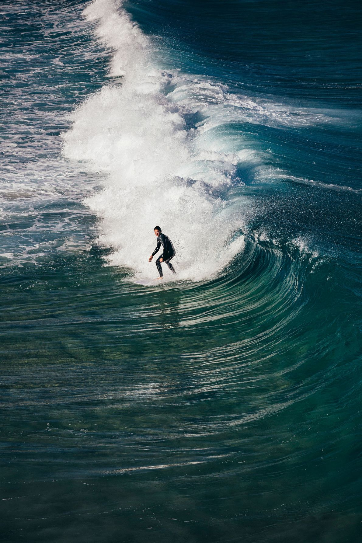 A surfer catches the waves at Bells Beach, a renowned surfing spot in Surf Coast Shire, ...