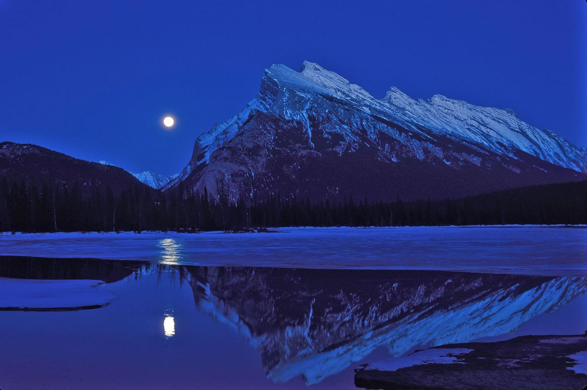 A full moon rises over Vermilion Lakes beside Mount Rundle in Banff National Park, Canada, during ...