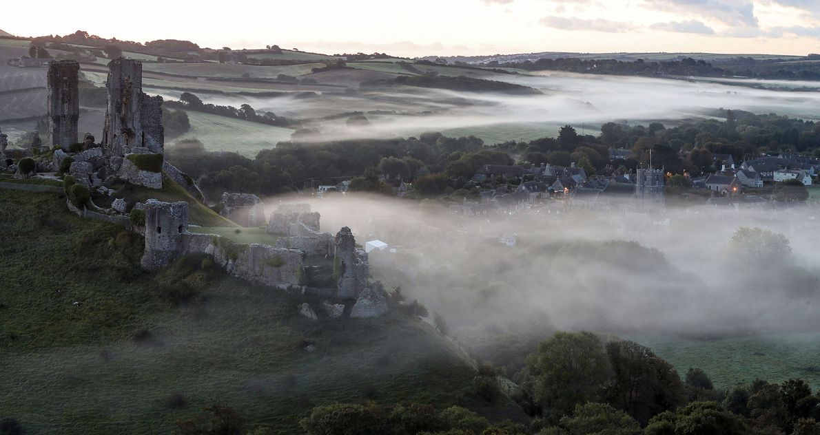 A low-lying mist surrounds the village of Corfe Castle in Dorset, England, as dawn breaks on ...