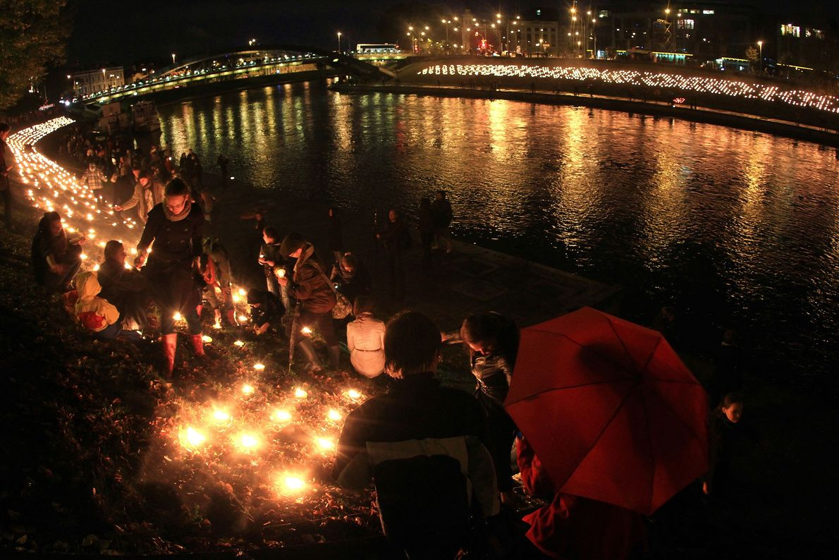 People light candles after sunset during the autumn equinox celebration at the Neris River waterfront in ...