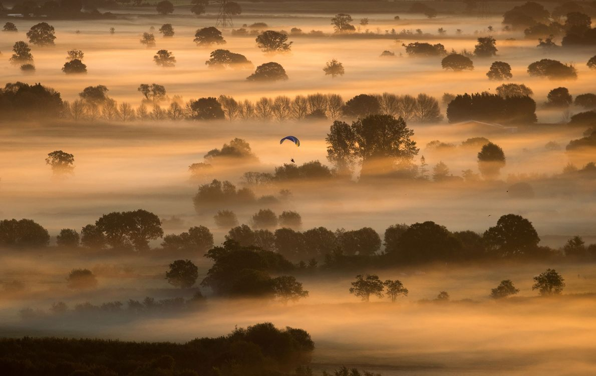 Early-morning mist lingers in fields as the sun rises over the Somerset Levels, as seen from ...