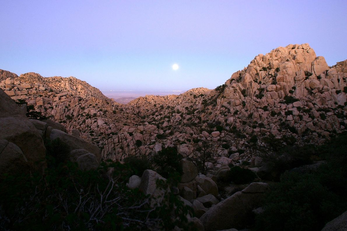 A full harvest moon marks the autumnal equinox as it rises over a desert mountain landscape ...