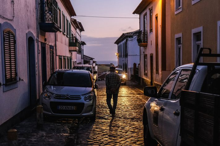 As night falls in Angra do Heroísmo, a resident takes an evening walk alone toward the ...