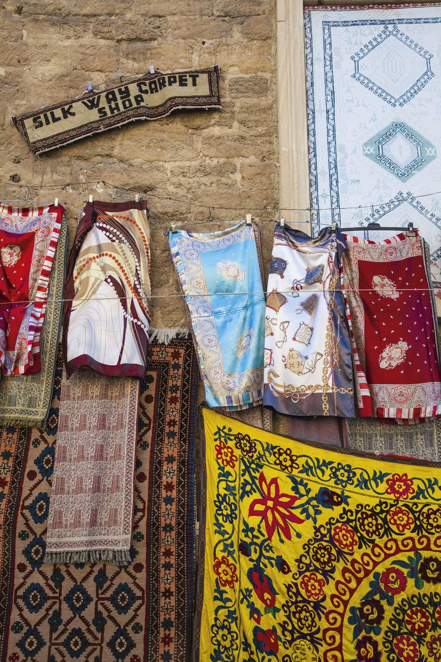 Traditional silk scarves and rugs for sale at Silk Way Carpet Shop in the Old City.