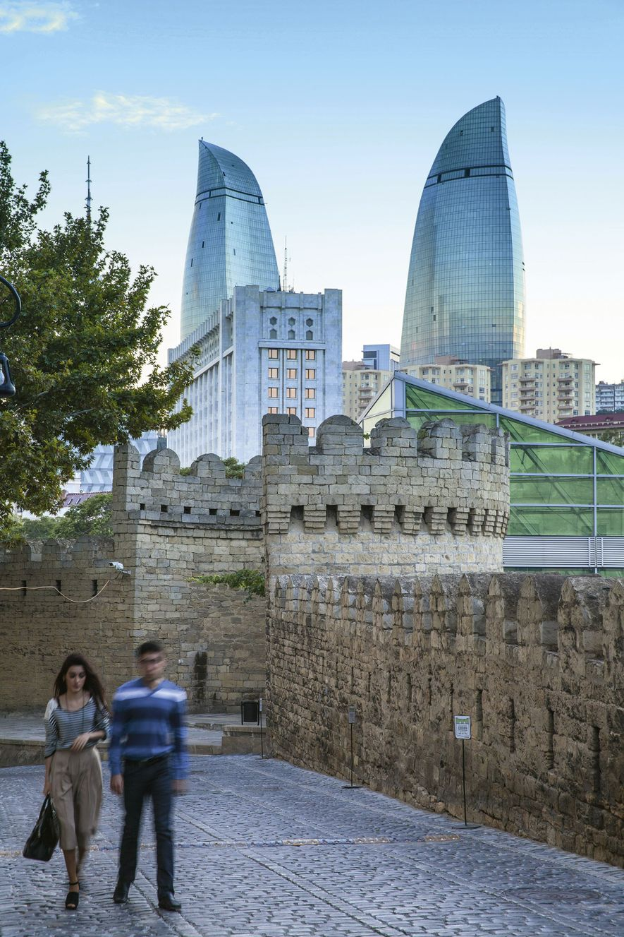 Locals strolling the city's ancient city walls with the Flame Towers piercing the sky in the ...