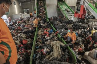 Workers load plastic materials to be washed and shredded at Re Pal Recycling facility in Pasuruan, ...
